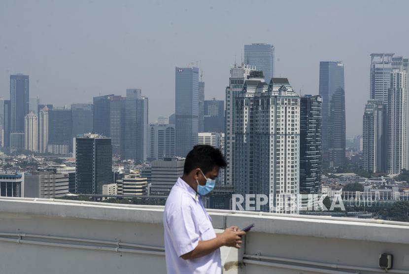 Petugas beraktivitas dengan latar belakang gedung-gedung bertingkat yang diselimuti polusi di Jakarta, Selasa (28/7). Polusi udara kembali menyelimuti langit Jakarta, sejak masa Pembatasan Sosial Berskala Besar (PSBB) memasuki masa transisi. Berdasarkan data AirVisual, kualitas udara Jakarta pada Selasa (28/7) mencapai angka 156 US AQI, yang tergolong tidak sehat.