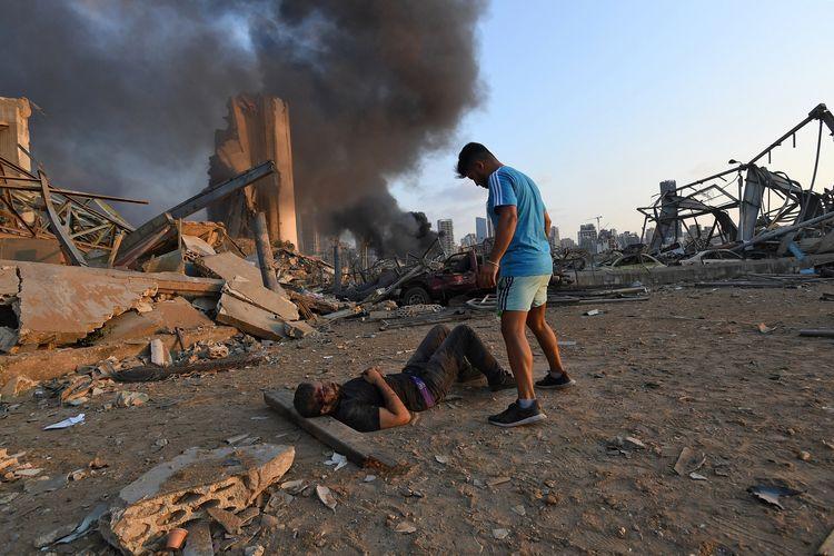 Seorang pria terluka tergeletak di tanah dengan kepulan asap di depannya, dalam insiden ledakan yang melanda ibu kota Lebanon, Beirut, pada 4 Agustus 2020. Petugas penyelamat mencari korban pada 5 Agustus 2020 di tengah kematian jumlah korban yang melebihi 135 orang.