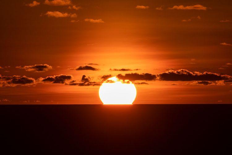 Matahari terbenam sempurna di lautan dilihat dari Bukit Paralayang Watugupit, Minggu (19/1/2020).